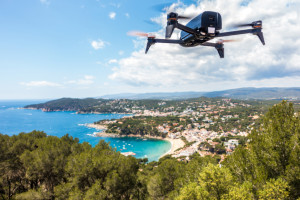 Llafranc, Spain. May 29, 2016. Parrot Bebop 2 Drone flying over the mountain in front of a coast city in costa brava, Spain